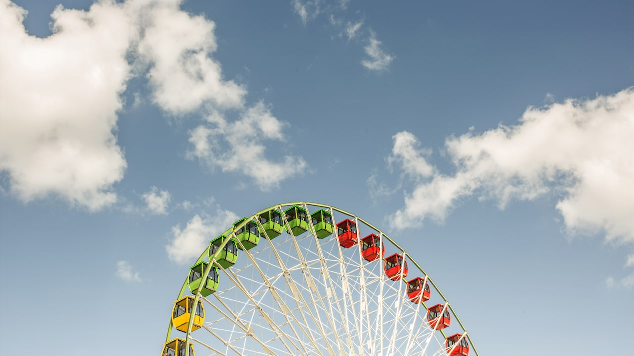 The top of a ferris wheel stands out in the foreground of blue skies and clouds.