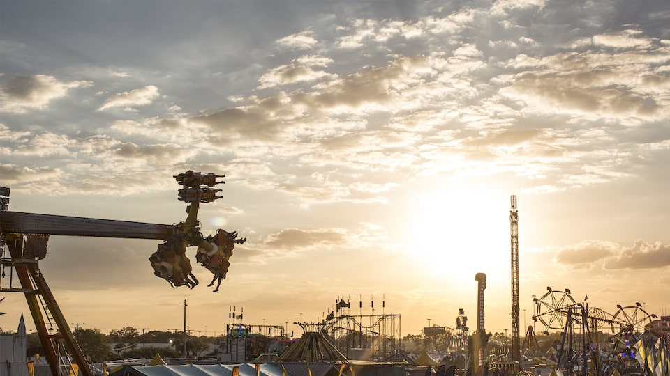 State fair rides jut into the sky as the sun sets.