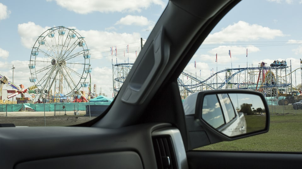 State fair rides seen through the windshield of a Chevy Silverado.