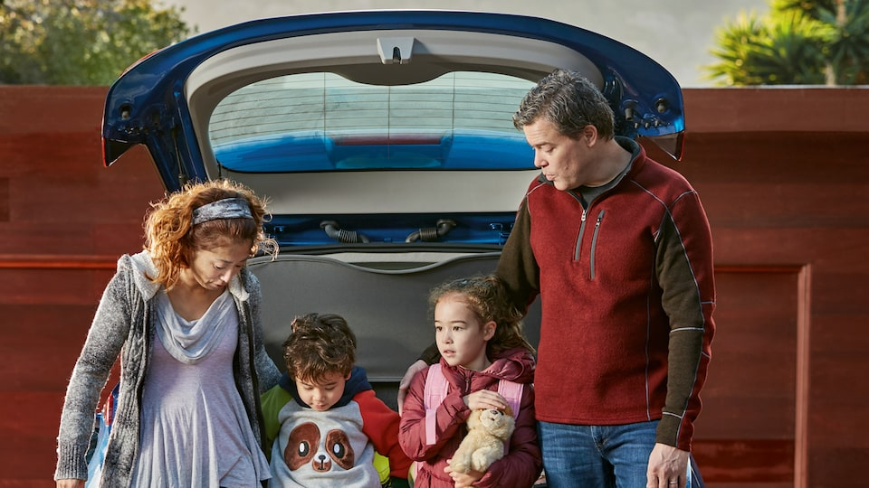 Ethan Stock with his wife and two kids standing at the back of their 2017 Chevy Bolt EV with the hatch open over their heads.
