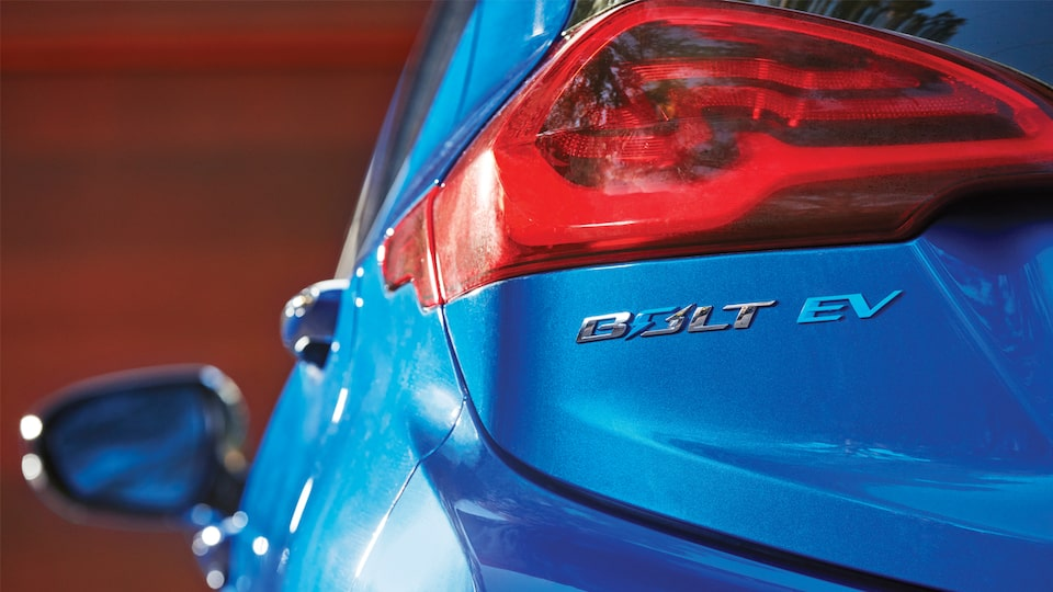Close-up of the rear of a blue 2017 Chevy Bolt EV showing a taillight and the Bolt EV badge.