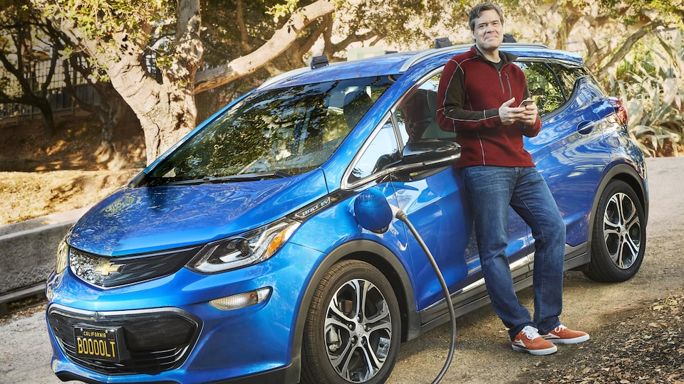 Ethan Stock standing next to his blue 2017 Chevy Bolt EV, which is plugged in to charge.