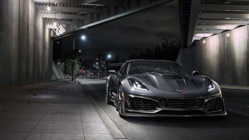 A black 2019 Corvette ZR1 seen from the front under a highway overpass with an empty street behind it.