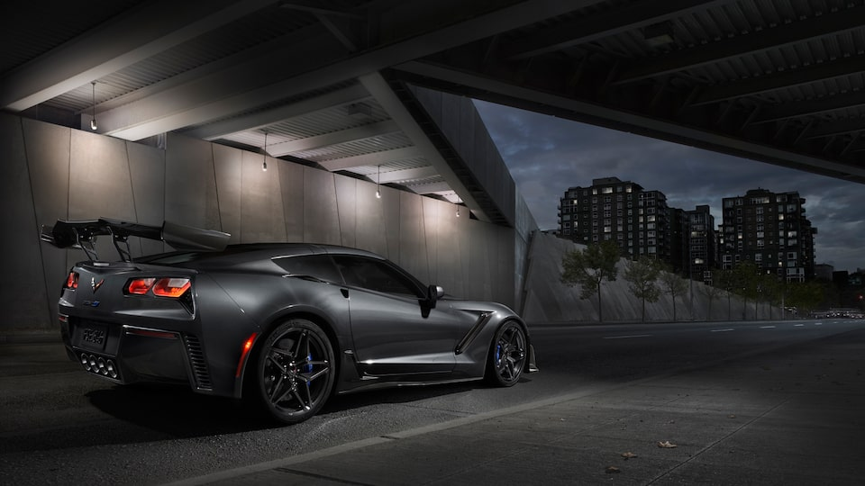 A black 2019 Corvette ZR1 with the available ZTK Performance Package seen from the right rear under a highway overpass, with red taillights glowing.