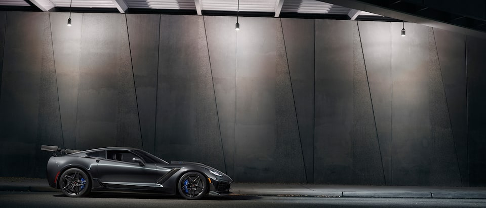A black 2019 Corvette ZR1 with the available ZTK Performance Package seen from the side in semi-darkness against the concrete wall of a highway overpass.