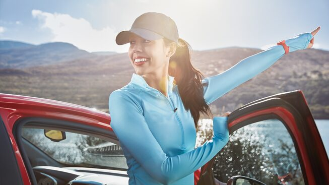A woman in a jogging outfit stands beside a Chevrolet Spark and points into the distance.