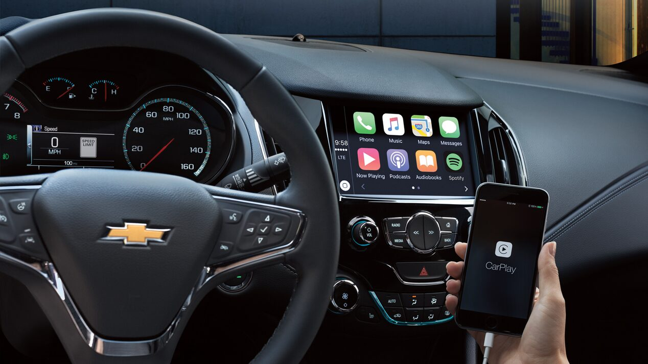 A hand holding a phone displaying the Apple CarPlay interface.