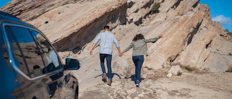 A couple holds hands while hiking up a rock formation.