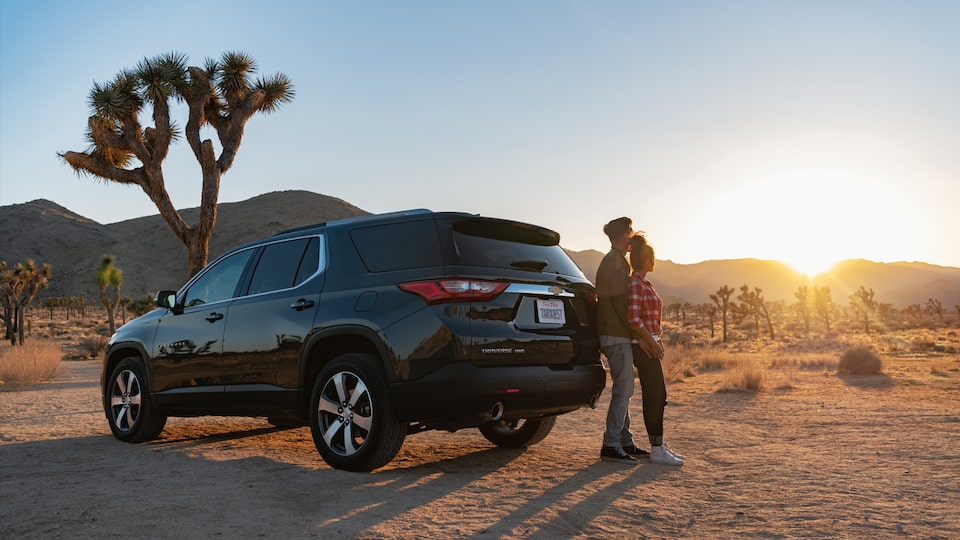 A couple standing behind the Chevrolet Traverse as the sun sets.