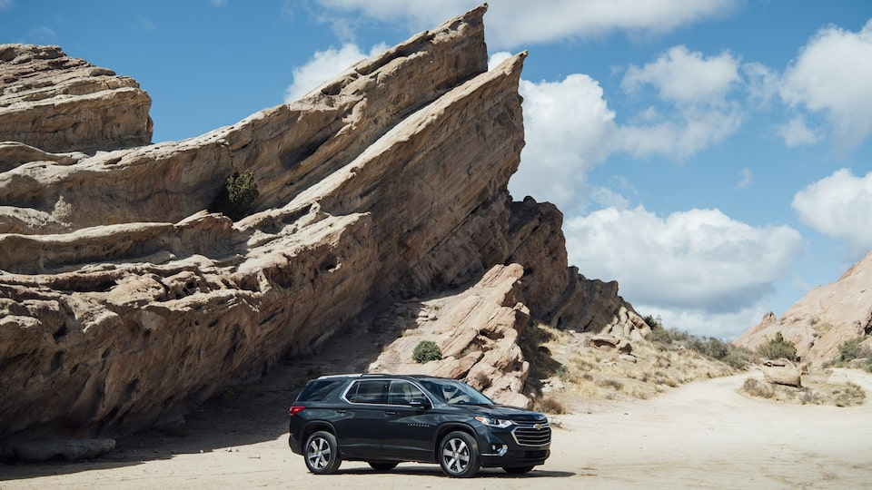 Chevrolet Traverse seen in a remote area in front of a rock formation.