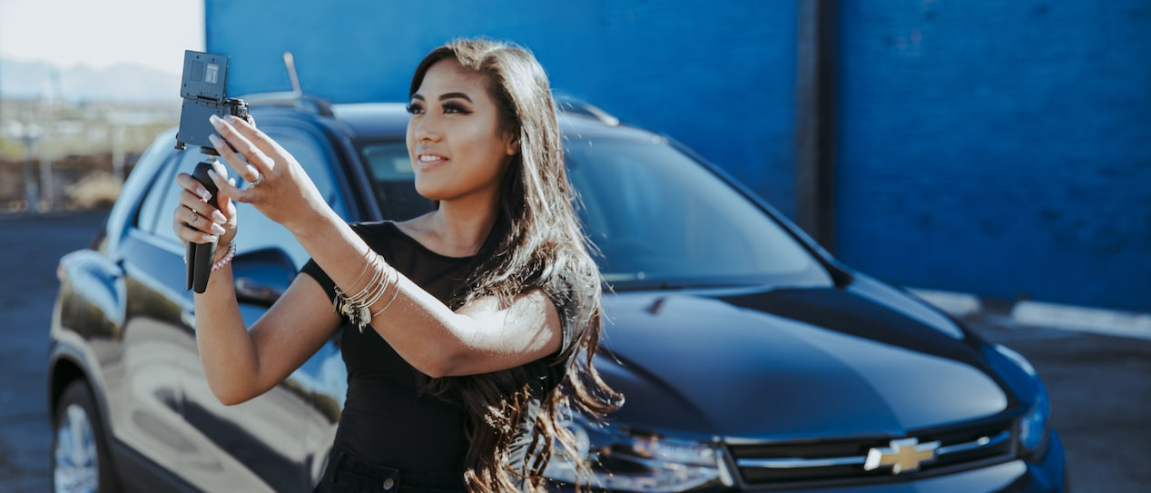 Vlogger Mo Calderon takes a self portrait in front of a Chevrolet Trax.