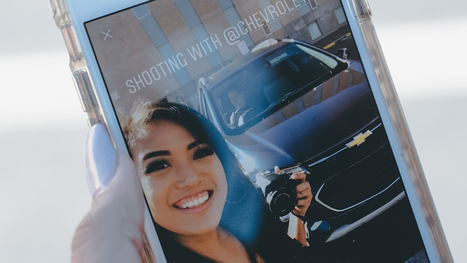 Mo Calderon's phone screen displays a self portrait in front of the Chevrolet Trax.