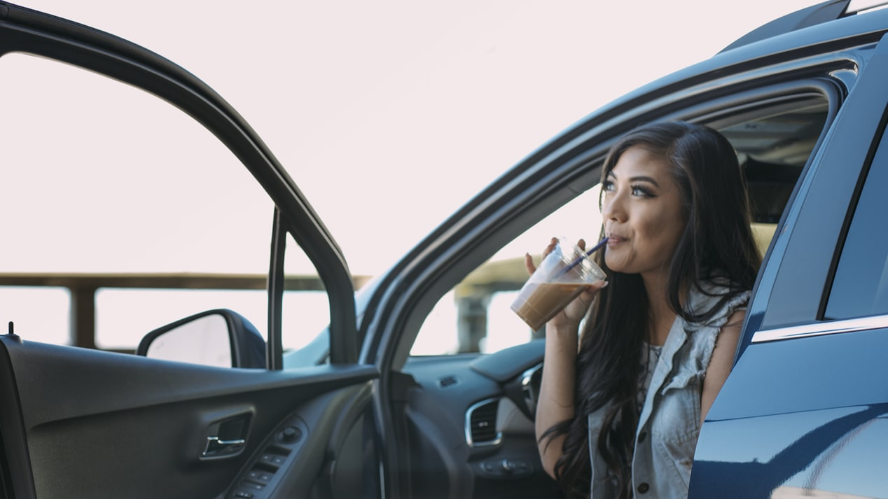 Vlogger Mo Calderon sips a cold coffee drink in the parked Chevrolet Trax.