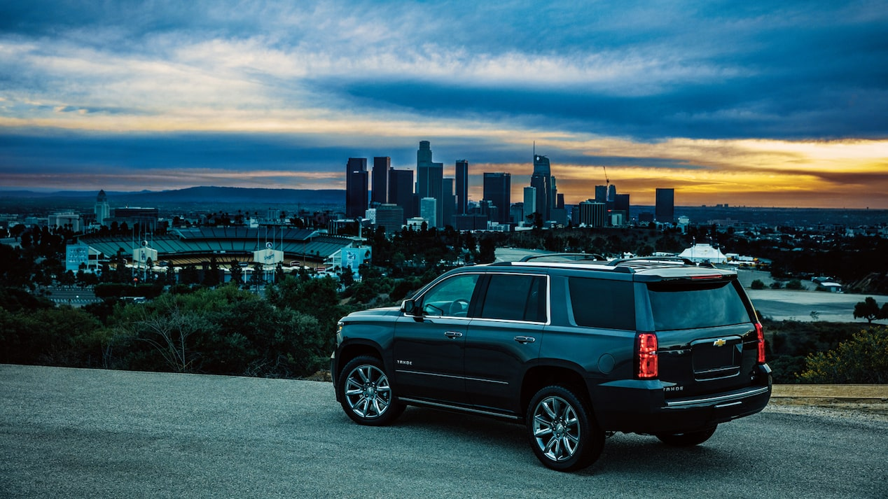A 2018 Chevy Tahoe at the side of a road on a hill overlooking the Los Angeles skyline.