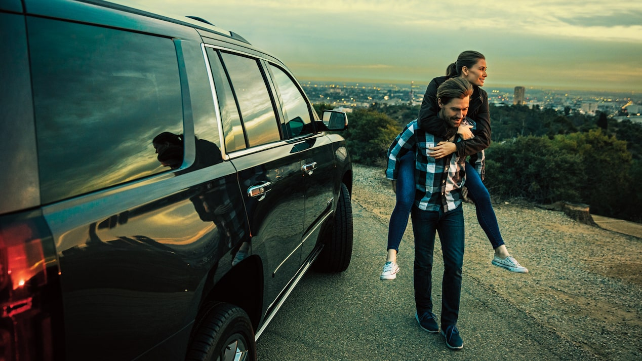 A couple standing next to a 2018 Chevy Tahoe on a hillside above Los Angeles.