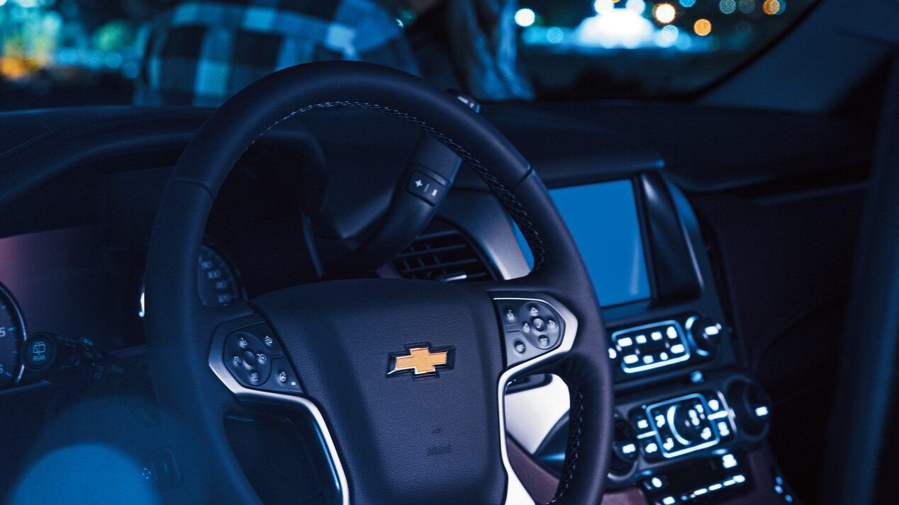 The interior of a 2018 Chevy Tahoe, shown at night with the lights of Los Angeles seen through the front windshield and two people standing next to the Tahoe.