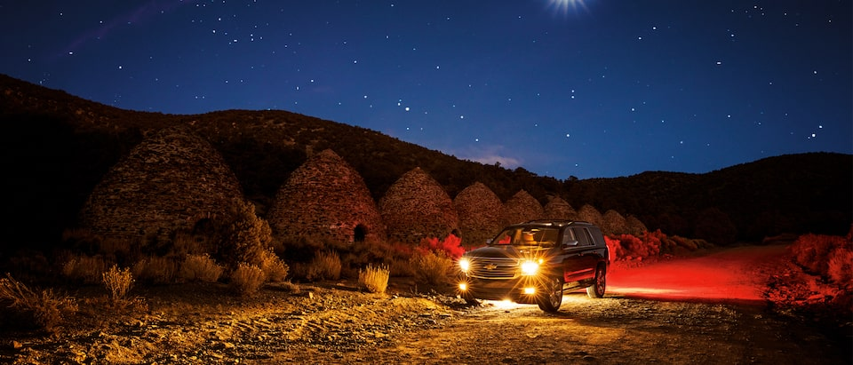 A 2018 Chevy Tahoe at night in the desert, with the stars and moon overhead and the landscape lit by the headlights and taillights of the Tahoe.