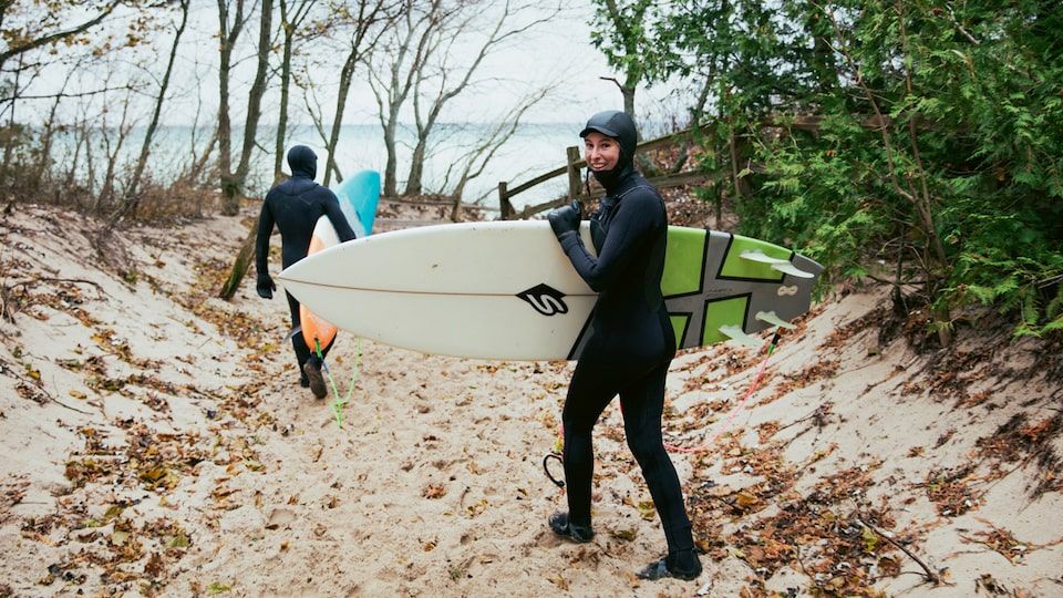 Two surfers in wetsuits walking down a sandy path toward Lake Michigan.