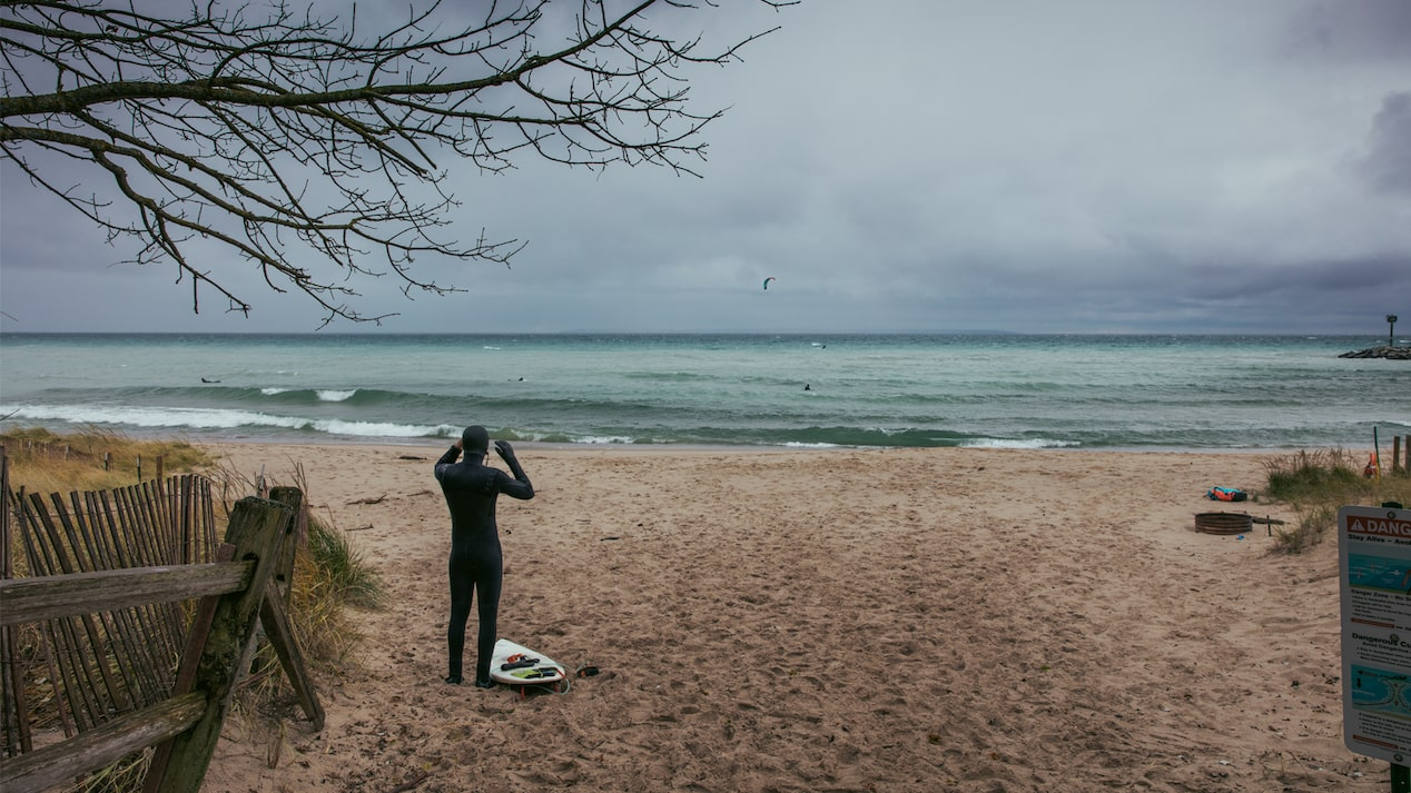 A surfer in a wetsuit stands on a Lake Michigan beach looking out at the water and gray sky.
