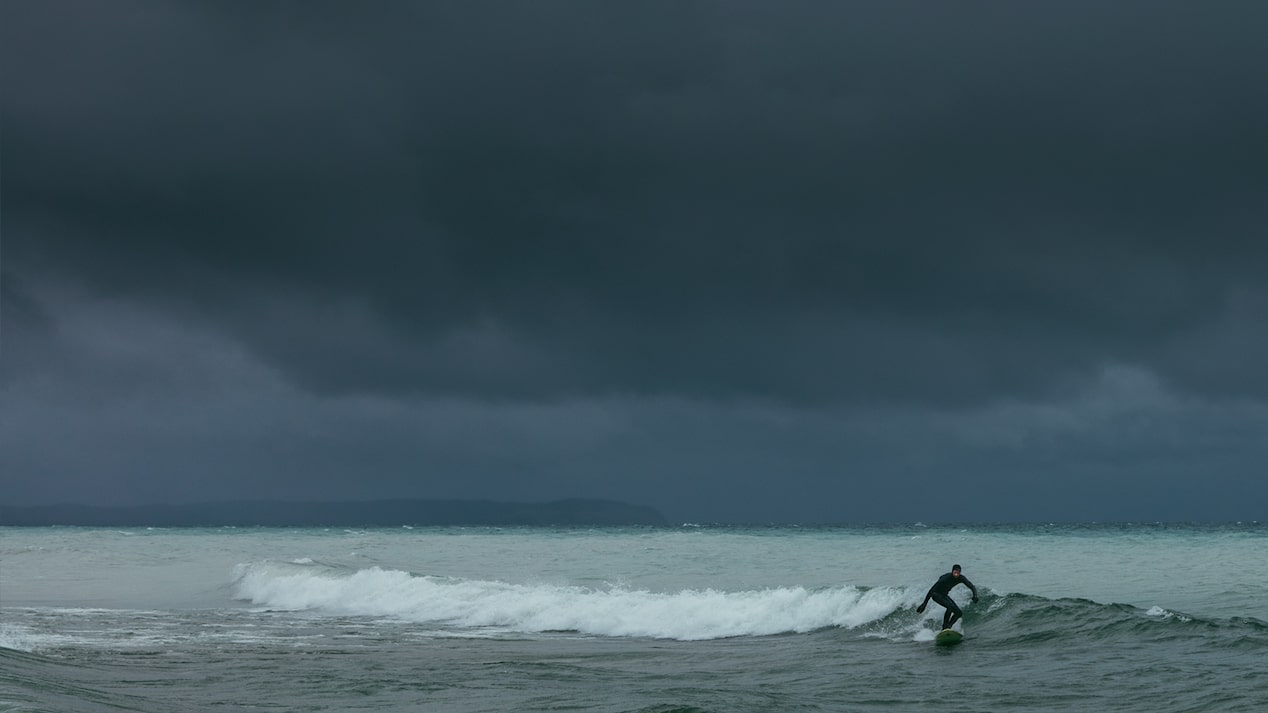 A surfer rides a wave in on dark Lake Michigan water with an ominous gray sky behind him.
