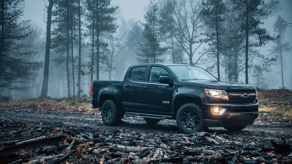 A 2018 Chevy Colorado Z71 Crew Cab Short Box with available Z71 Midnight Edition package, sitting in a foggy, wooded area.