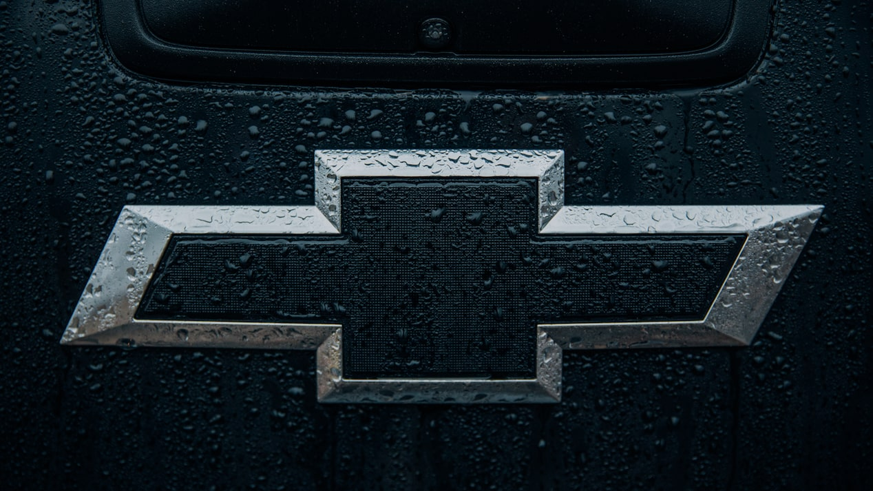 The black and silver Chevrolet bowtie logo spattered with rain on the back of the Colorado Z71 Crew Cab Midnight Edition.