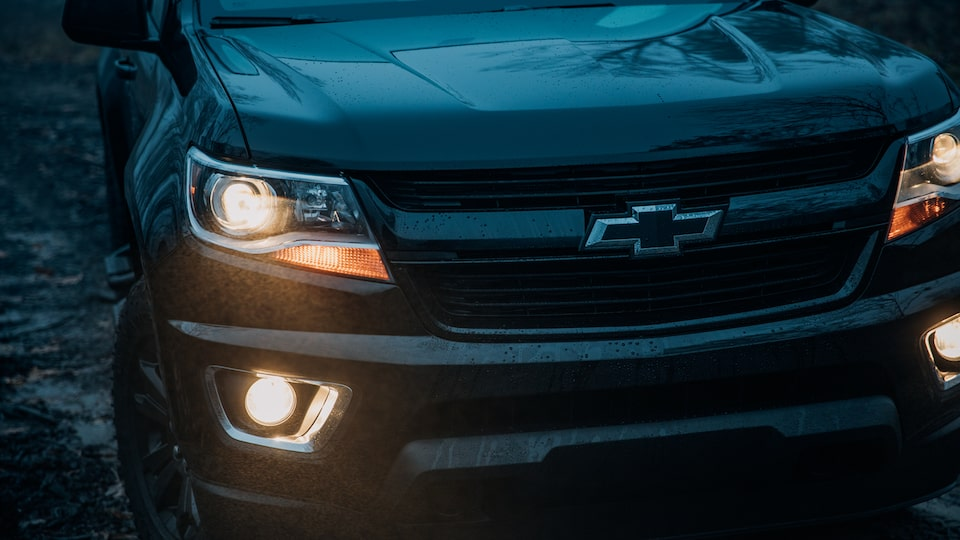 The front end of a black Chevy Colorado Z71 Crew Cab Midnight Edition in semi-darkness with headlights and foglamps glowing.