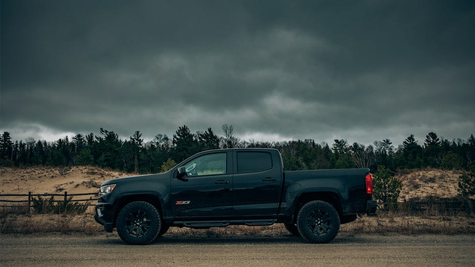 A black Chevy Colorado Z71 Crew Cab with the Midnight Edition package seen from the side in front of Lake Michigan sand dunes.