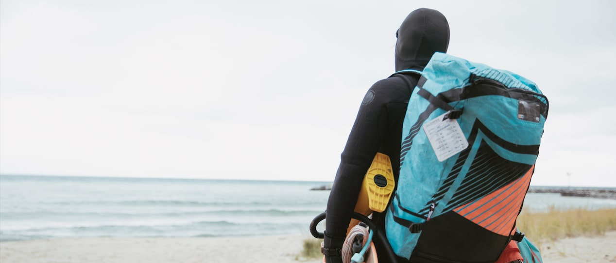 A person in a full wetsuit walking across the beach toward Lake Michigan with a full backpack and carrying gear.