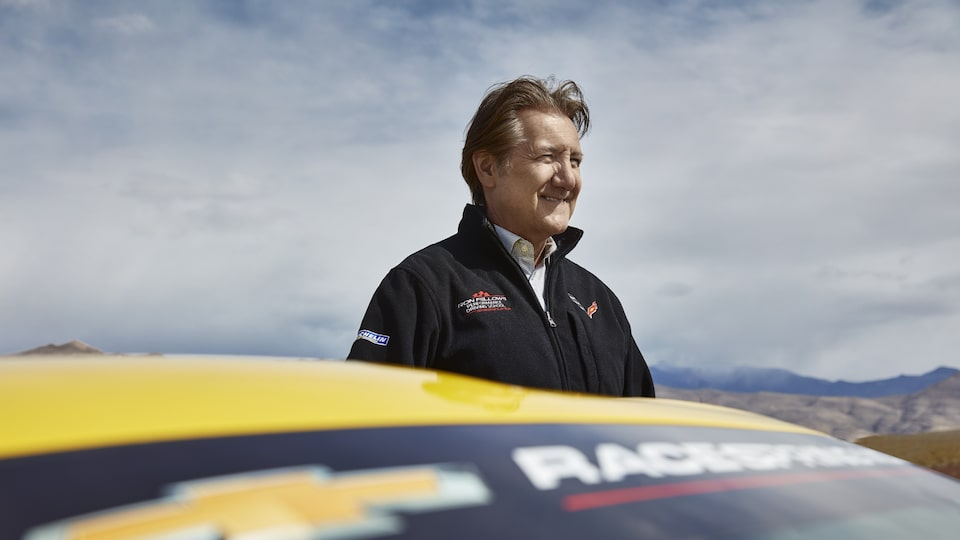 Ron Fellows behind a yellow Corvette.