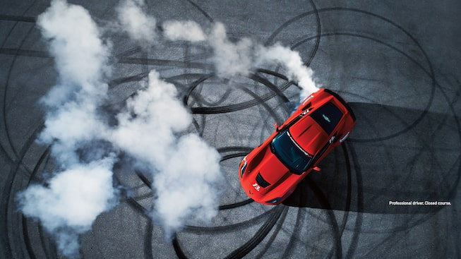 Overhead shot of a red Corvette doing donuts on a closed course.