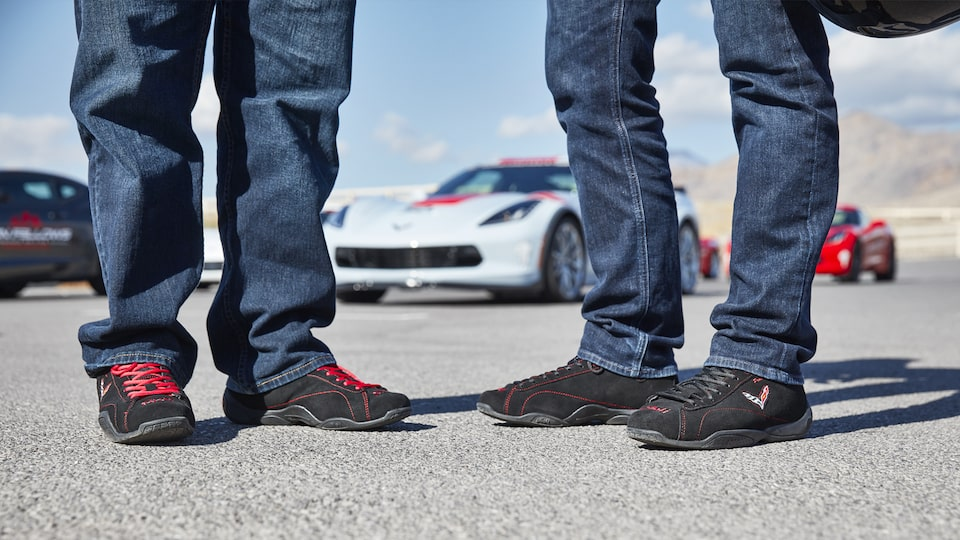 Two students feet as they stand on the track, with Corvettes behind them.