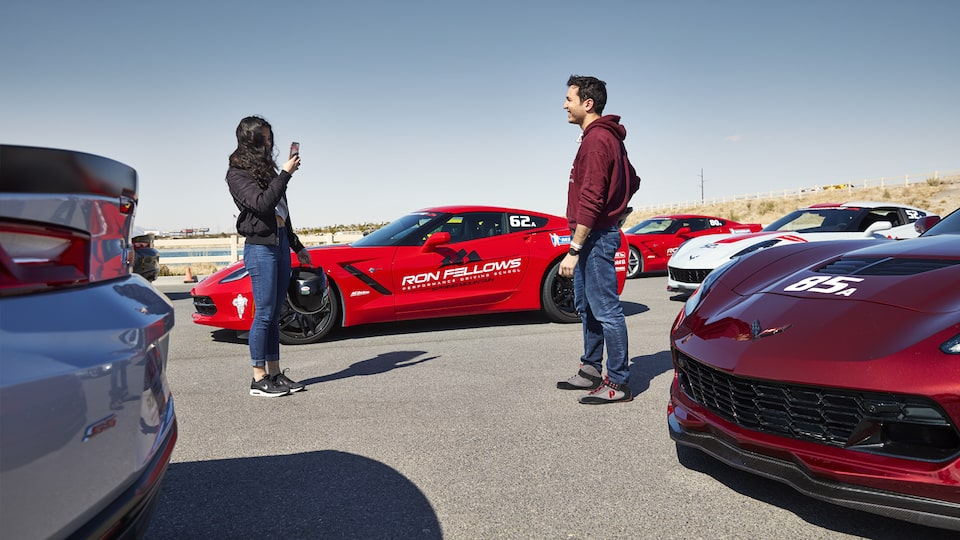 Students stand and talk next to a red Corvette.