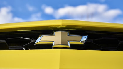 The Chevrolet bowtie emblem on the grille of a yellow Camaro.