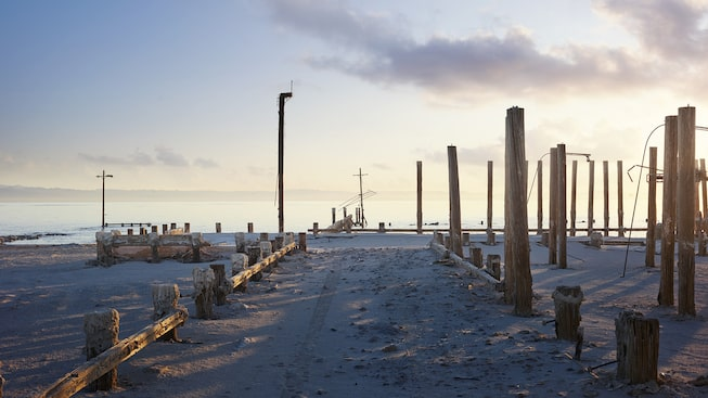 The sand-covered road leading into Salton Sea, California, ends at the posts of a long-gone pier.