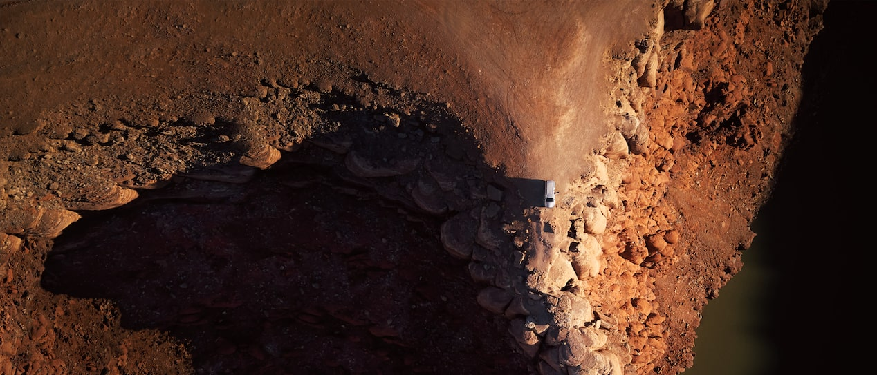 An aerial shot of a Chevrolet SUV at the end of a desert road.