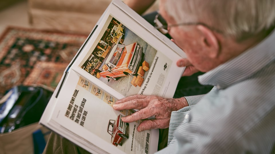 Paul Hitch looks through classic ads for some of the trucks he helped engineer.