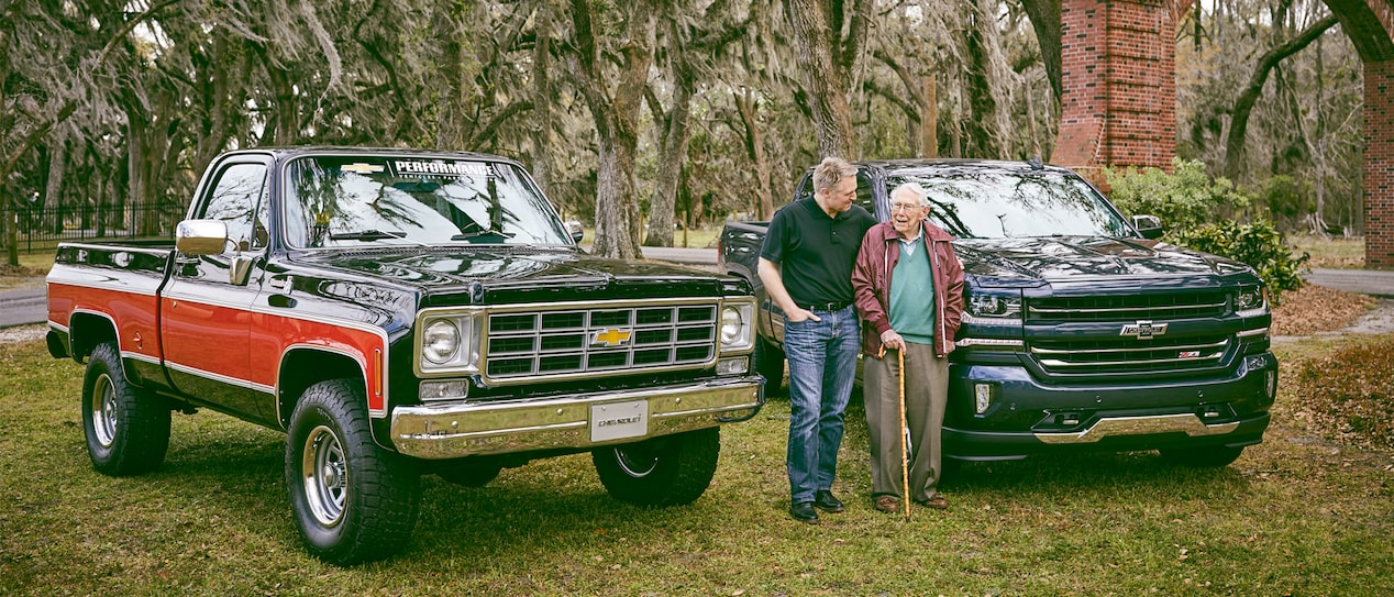 Eric Stanczak and Paul Hitch stand and talk between a classic Chevy truck and a Chevy Silverado Centennial Edition.