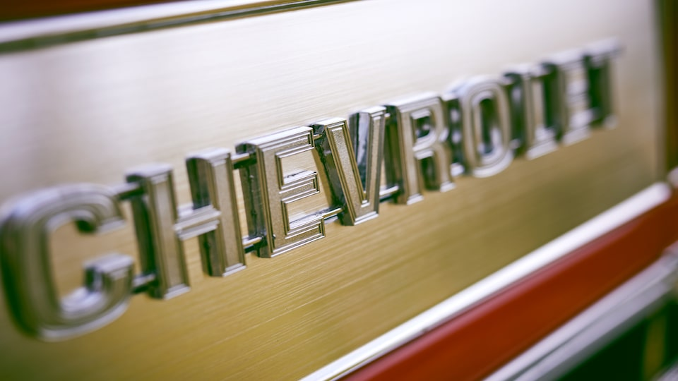 A Chevrolet emblem on the tailgate of a classic Chevy pickup.