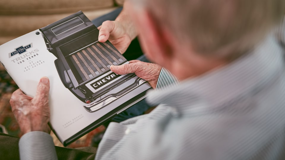 Paul Hitch examines a book of historical Chevy truck advertising.