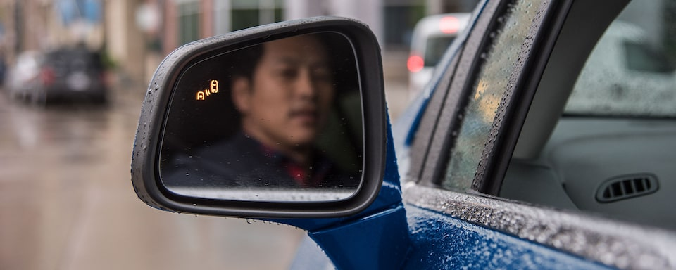 Chevy Safety: Man looking in side rearview mirror
