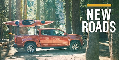 A Chevy Colorado with two kayaks on its rack drives through the forest