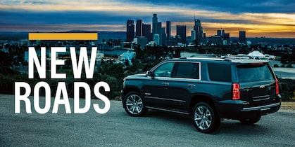 "A Chevy Tahoe at the side of a road overlooking the skyline of Los Angeles at sunset. The words ""New Roads"" are over the image."
