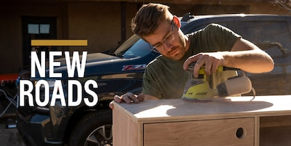 A man sands a woodworking project with a 2019 Chevy Silverado in the background.