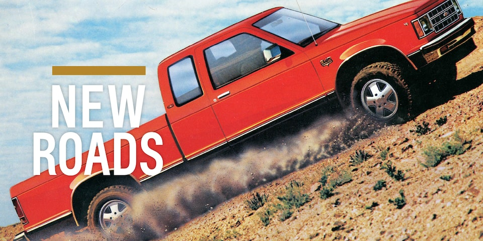 "In a photo from the 1983 brochure, a two-tone red and black Chevy S-10 pickup kicks up dirt as it drives across a desert terrain. Text over image reads ""New Roads."""