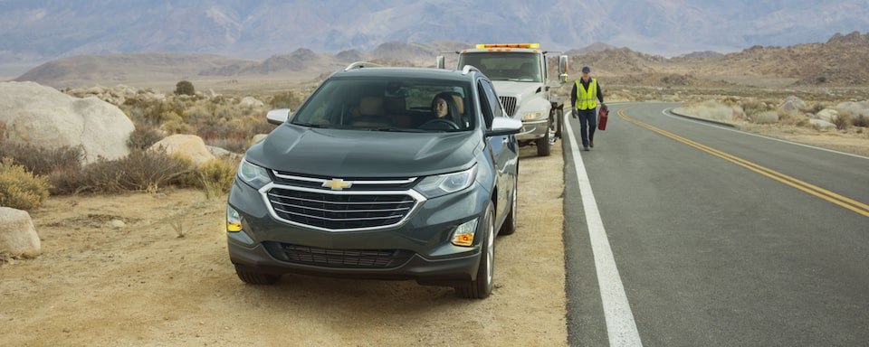 A Chevrolet vehicle broken down on the side of the road getting help from roadside assistance