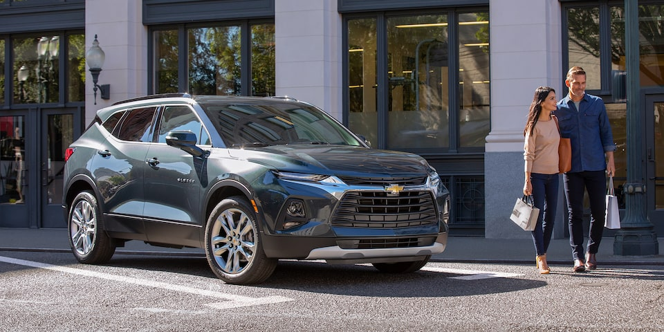 A man and a woman walking near the 2020 Chevy Blazer Sporty SUV