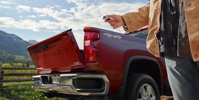A man uses the 2020 Chevy All-New Silverado HD Truck key fob to open the tailgate automatically