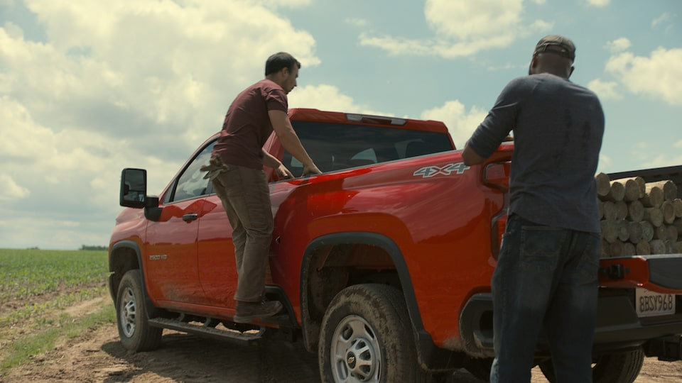 Two men uses the 2020 Chevy All-New Silverado HD Truck bed to load lumbers video still