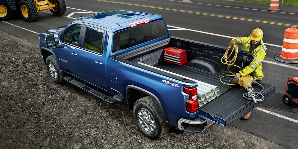 Two men using the 2020 Chevy All-New Silverado HD Truck bed for commercial work